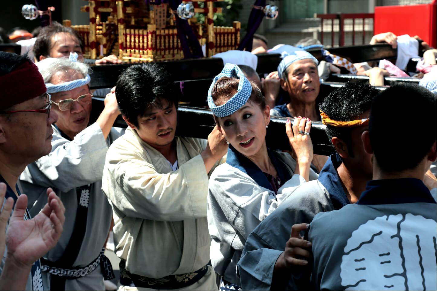 女性も法被を着てお神輿を担ぐ